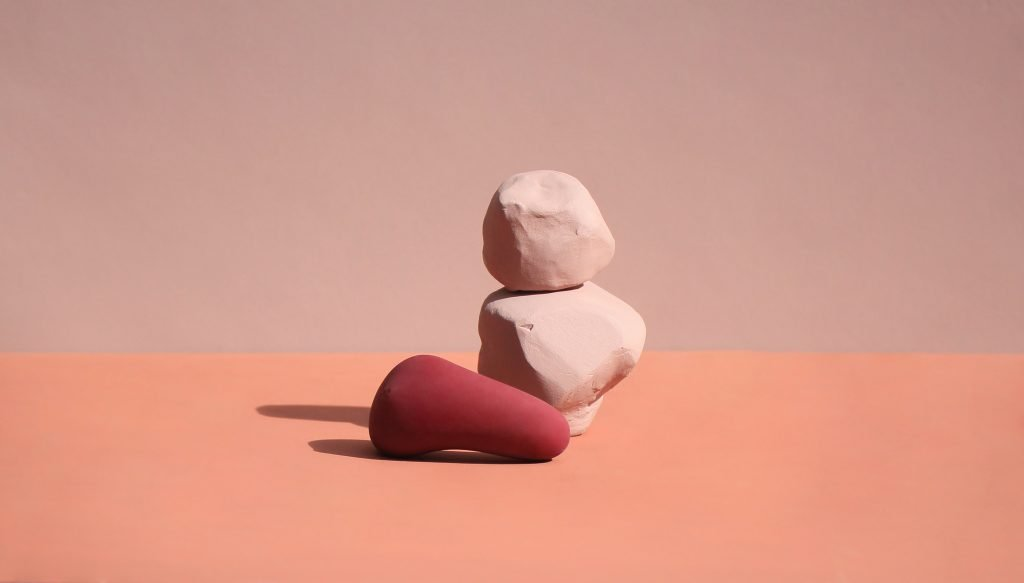 Photograph of the Frida sex toy laid down infront of two different shaped pastel peach painted rocks. The background is a very light peach wall and the floor is a darker shade of painted pastel peach. There are shadows from the objects. The Friday sex toy is a darker red-like peach and is rounded at one end and curves round into a pointed cone shape.
