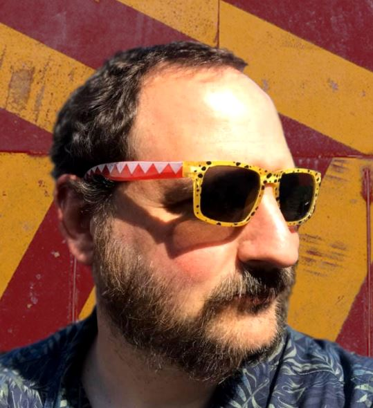 Ed is standing in front of a funky burgundy and egg-yolk yellow chevron background. He's soaking up the sun with his funky red and yellow patterned shades and leafy blue sumer shirt, the sun striking his glasses in a way that leaves shadows on his face and beard.