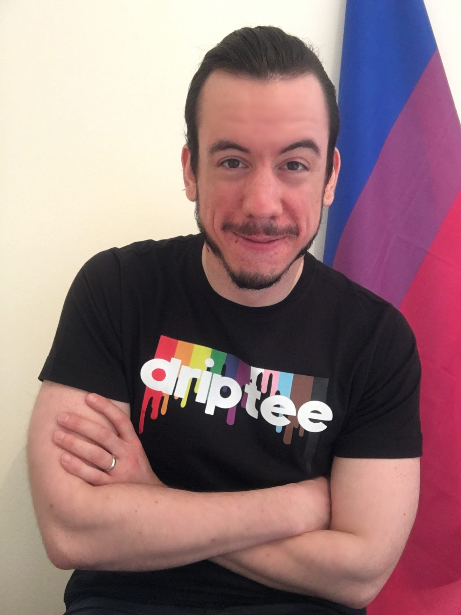 a smiling man (Mark Stokes) crossing his arms while wearing a black tee with DRIPTEE written on it and a Bi flag behind him. photo by Mark Stokes]