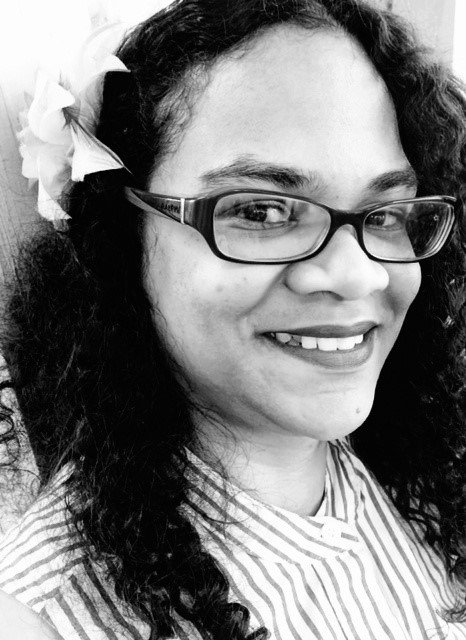 In black and white, Tamyka is side-on to the camera, a flower in the curly black hair that flows down over her shoulders. Reflections play on her black, thick-rimmed glasses, as she looks at the camera with a relaxed, confident smile.