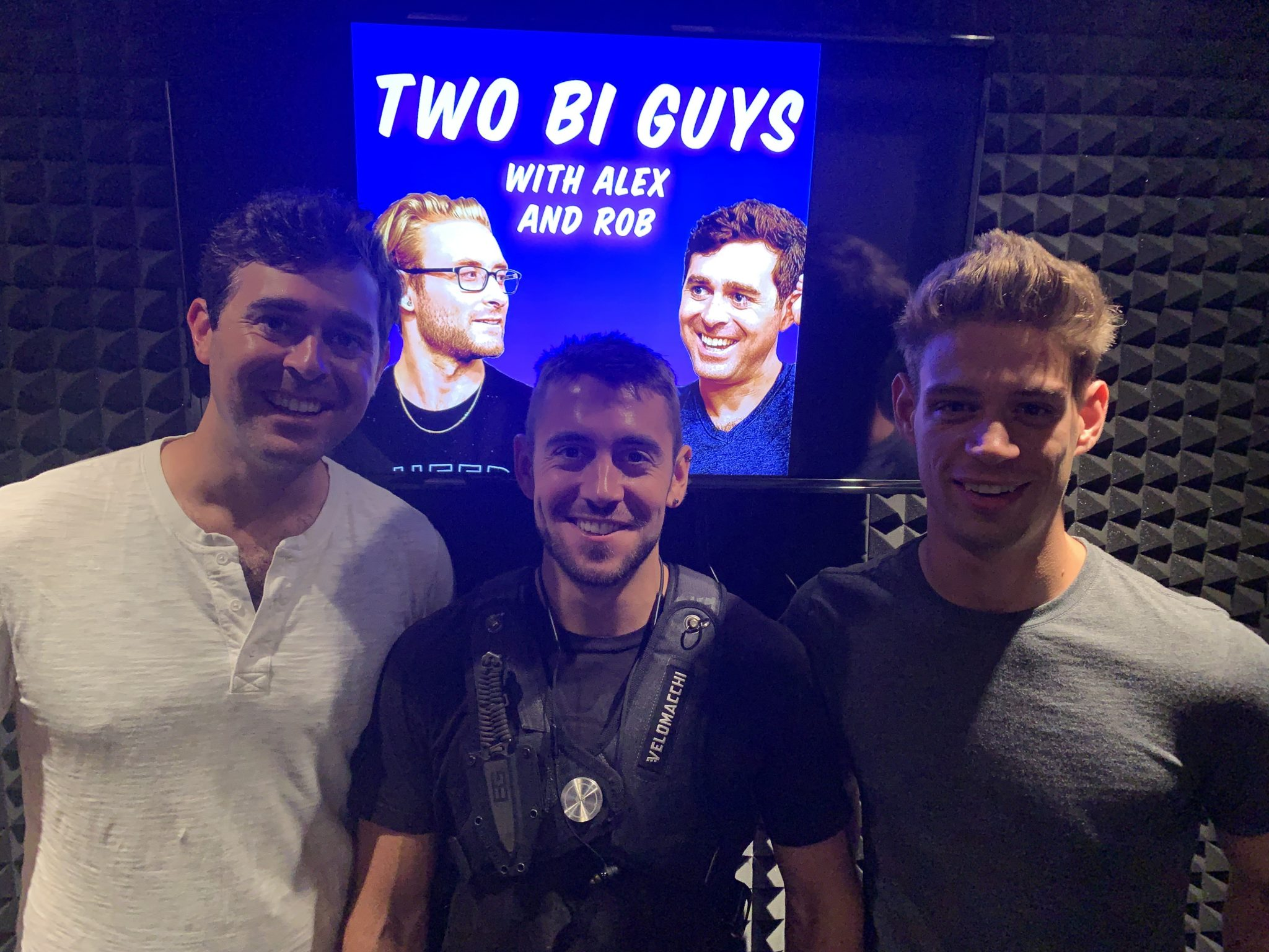three men standing next to each other (Alex Boyd, Dante Cole, Michael DelRay) in a soundbooth. one is wearing a white henley shirt, one is wearing a dark tee with a harness over it, & the last is wearing a grey tee. photo by Rob Cohen