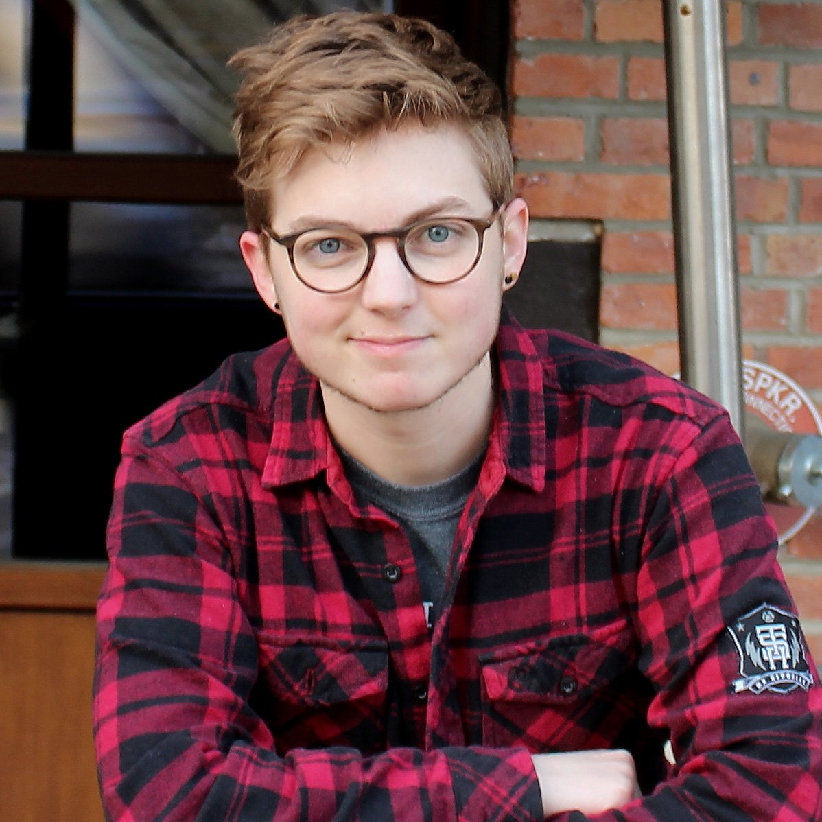 a picture of Jackson Bird. He is wearing a red flannel top and grey t-shirt underneath. He has short brown hair and wears glasses