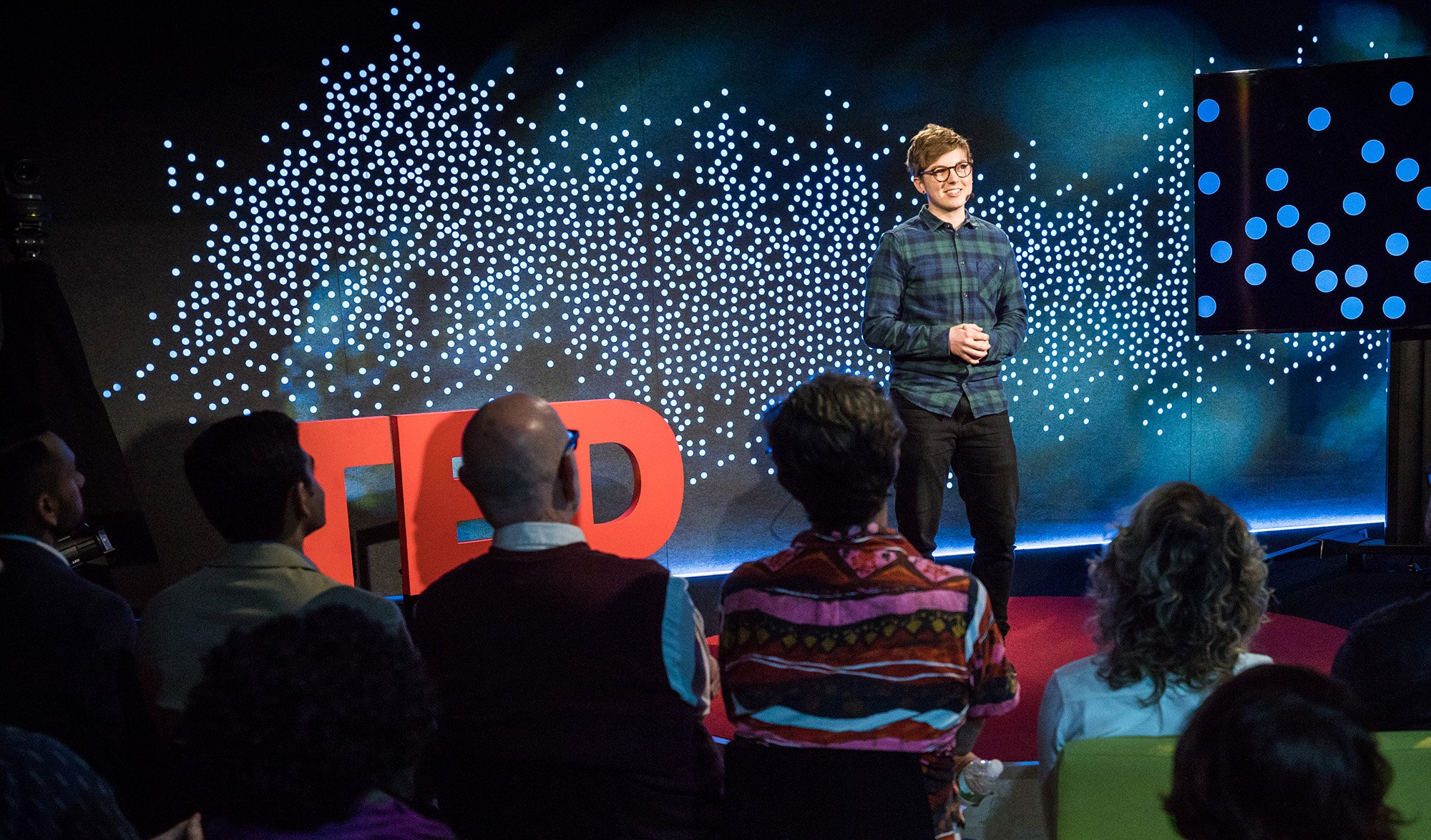 a picture of Jackson Bird on the TedTalk Stage. He stands in front of a crowd, wearing a blue and green flannel top and jeans.