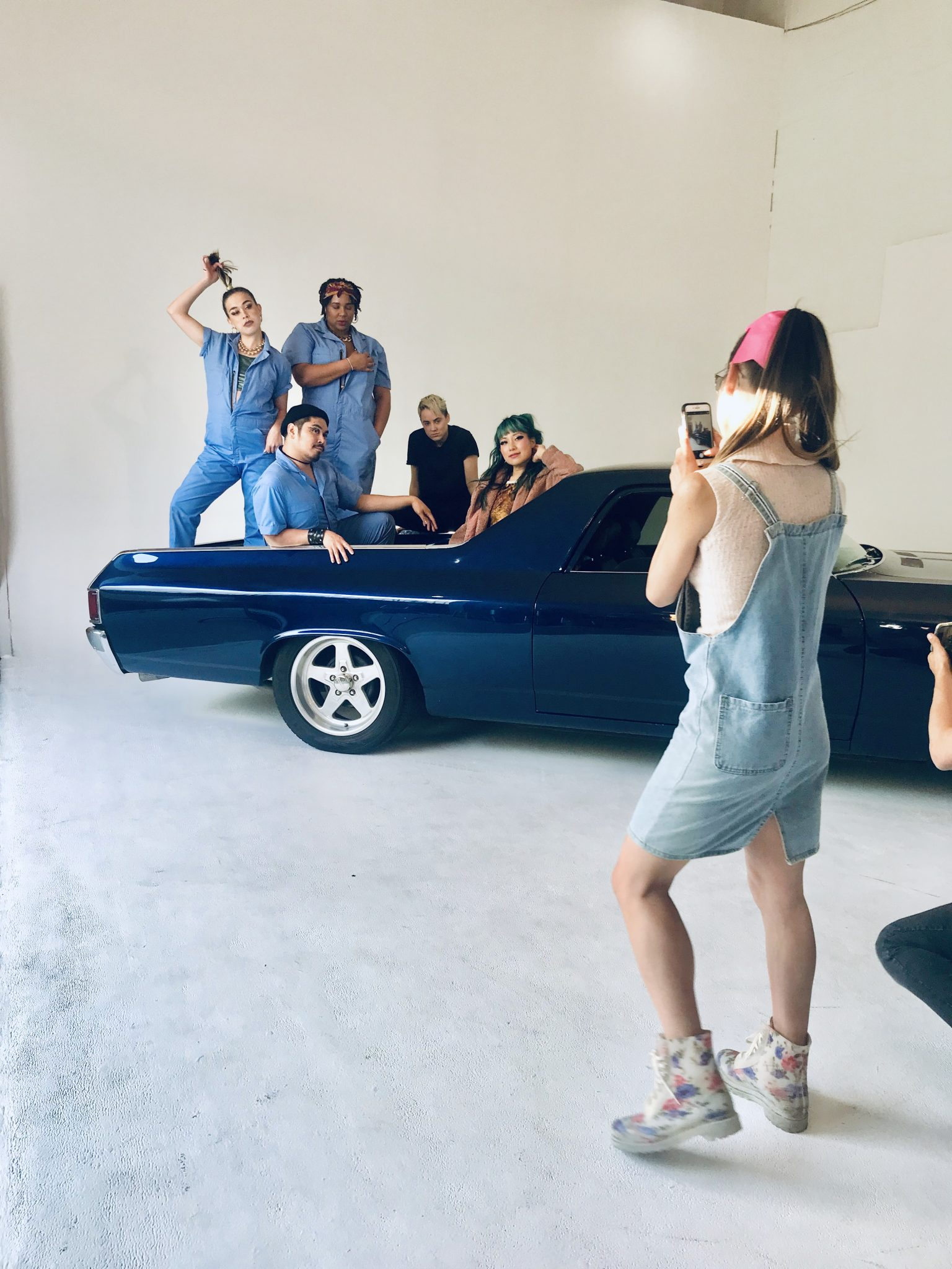 Colour photograph from, the Another Life music video. It features Polartropica sat in the hatchback of a dark blue car which is in a studio setting. Around them are 4 other people. 1 is the blonde short haired love interest and the other 3 are mechanics dressed in blue overalls. They all post for a photograph being taken on a phone by another person in the front right corner of the photo. They wear blue denim dungarees, floral boots, a pale top and pink bow in their hair.