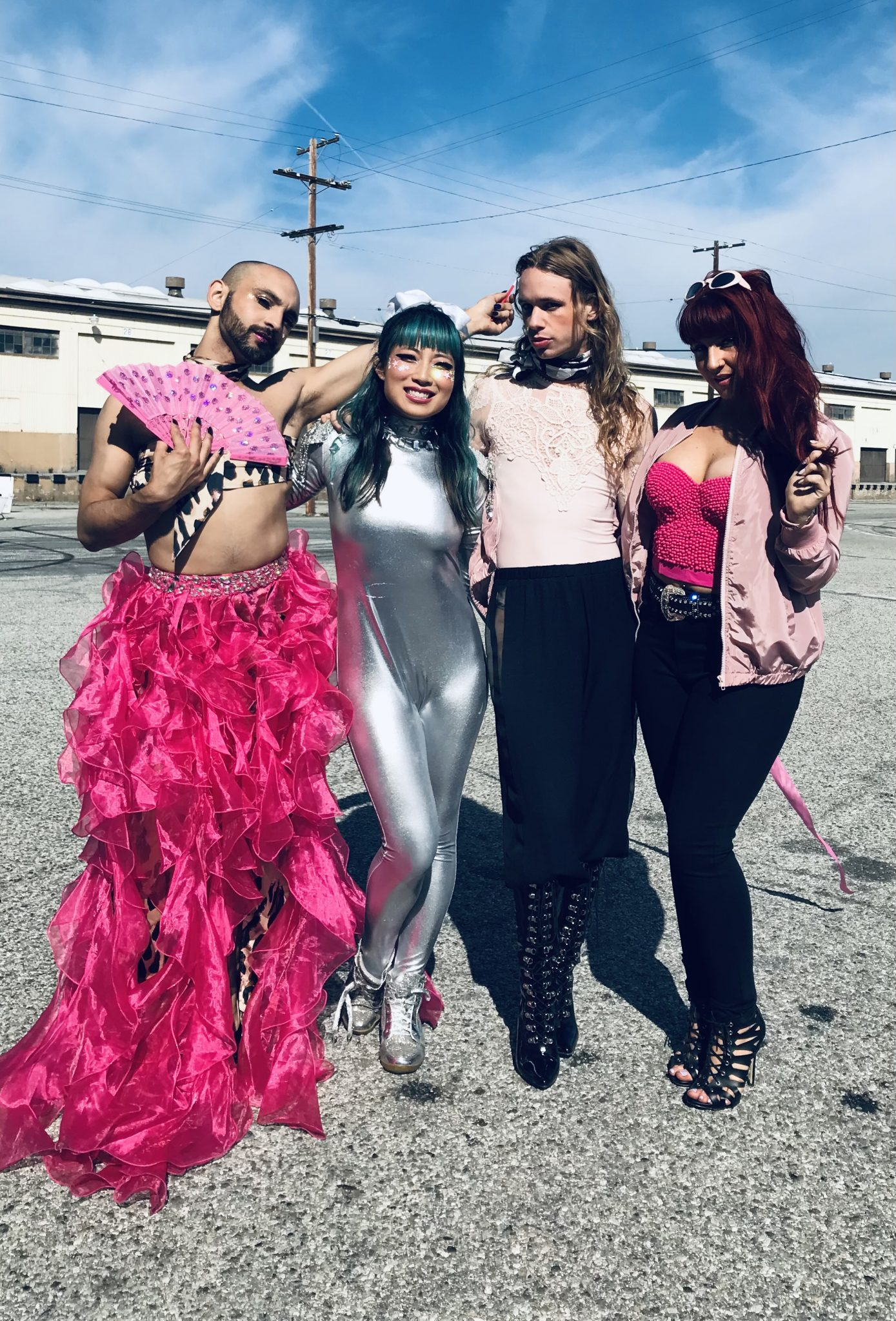 Colour behind the scenes photograph from, the Another Life music video. It features Polartropica with other people. The person to their right is holding a pink fan, and wearing a bright pink feathered skirt, leopard print crop top. They have no hair on their head and a dark haired trimmed beard. Polartropic is to their right wearing an all in one shiny silver bodysuit with their hair in a half up hair do with a bow. They are smiling at the camera. To their right are two other people. One with long brown hair wearing a pale top and dark trousers and tall buckled up boots.. The last one to the right wears a pink bomber jacket, bright pink top, sunglasses, dark trousers and heels. They are in a car park setting with blue sky, gravel flooring and a building behind them.