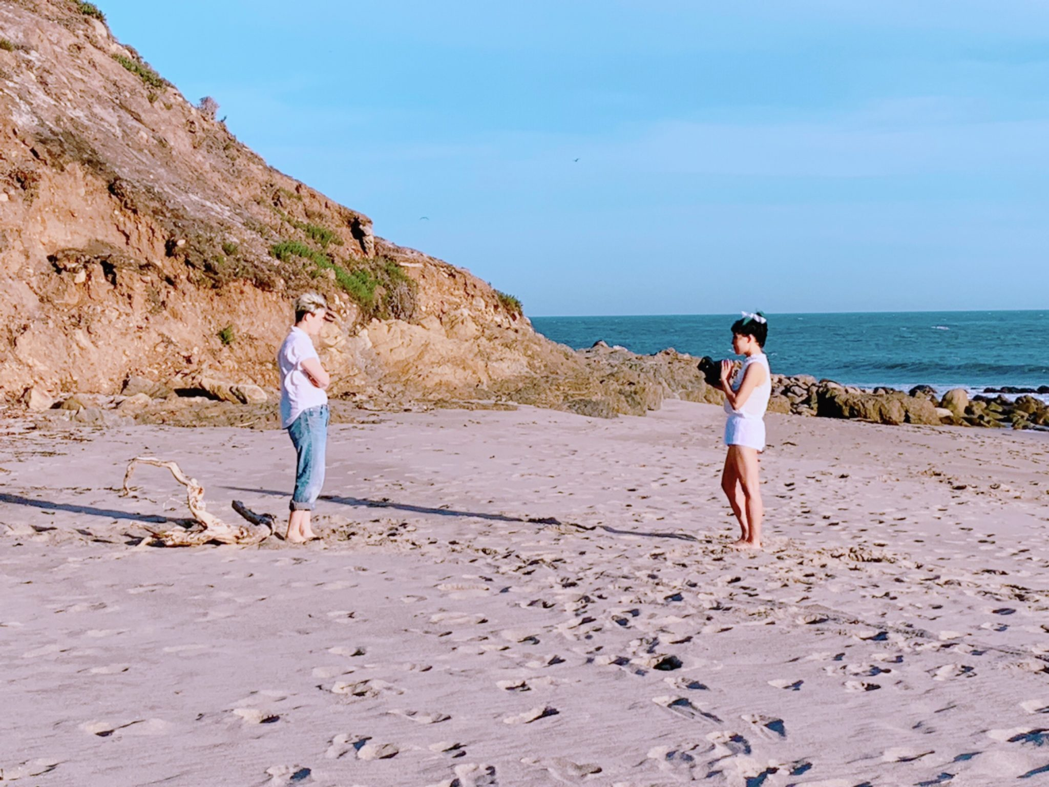 Colour photograph from, the Another Life music video. It features Polartropica on the right and their love interest on the left. They are stood apart on a well trodden beach. There is the sea to the right and a cliff to the left. The sky is clear and blue. Polartropica is wearing white shorts, top and bow in tied up hair. They are also carrying a camera which is pointing at the other person. The other person has blonde short hair and is wearing blue jeans and a white top, their arms are crossed in front of them.
