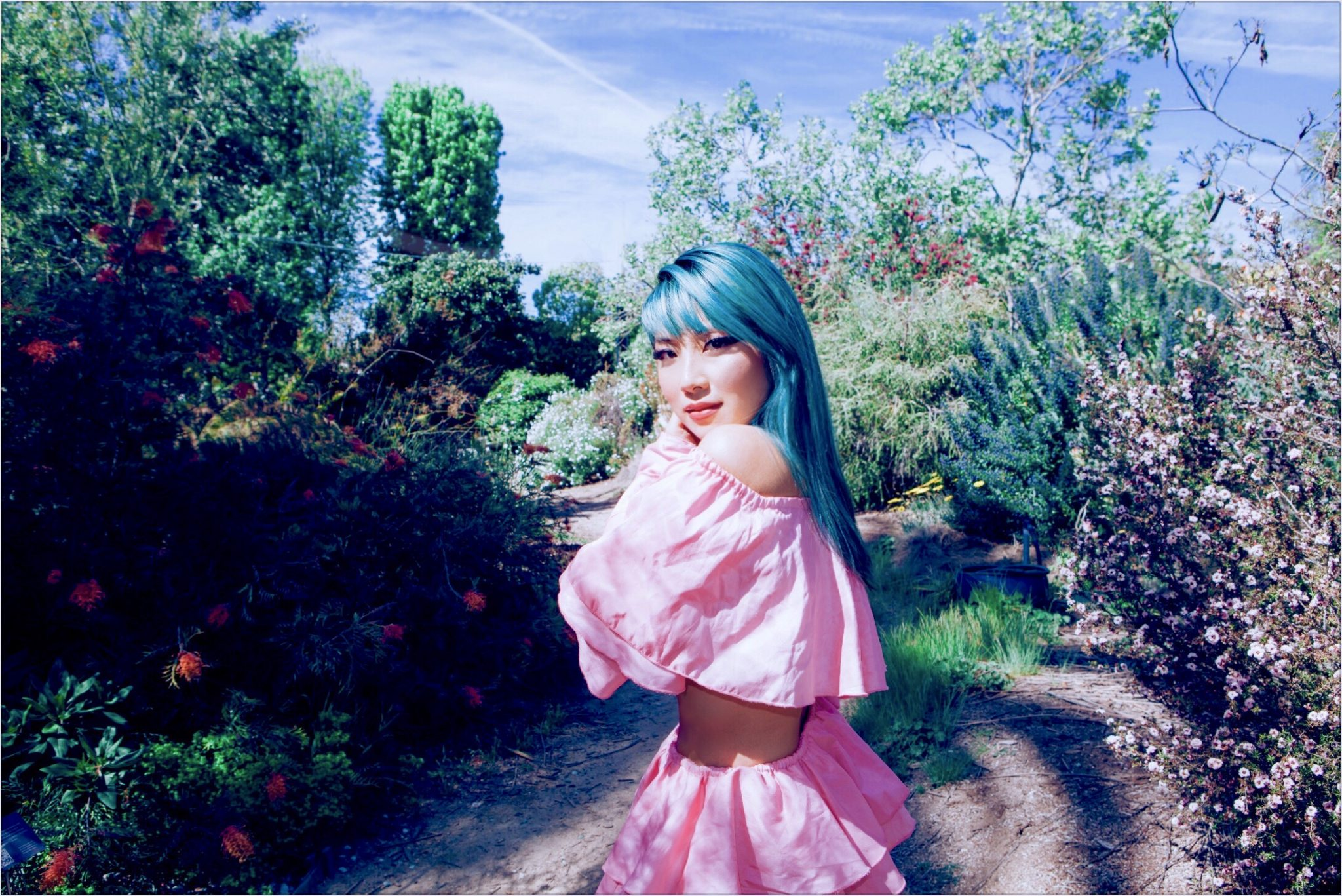 Colour photograph of Polartropica. They are stood outside surrounded by trees and plants. They have long turquoise hair with a fringe. They wear a crop top and layered skirt co-ord outfit in pastel pink. They have winged eyeliner and a peach lip stick on. They are side on and their arm is wrapped around them as they turn to look back at the camera.