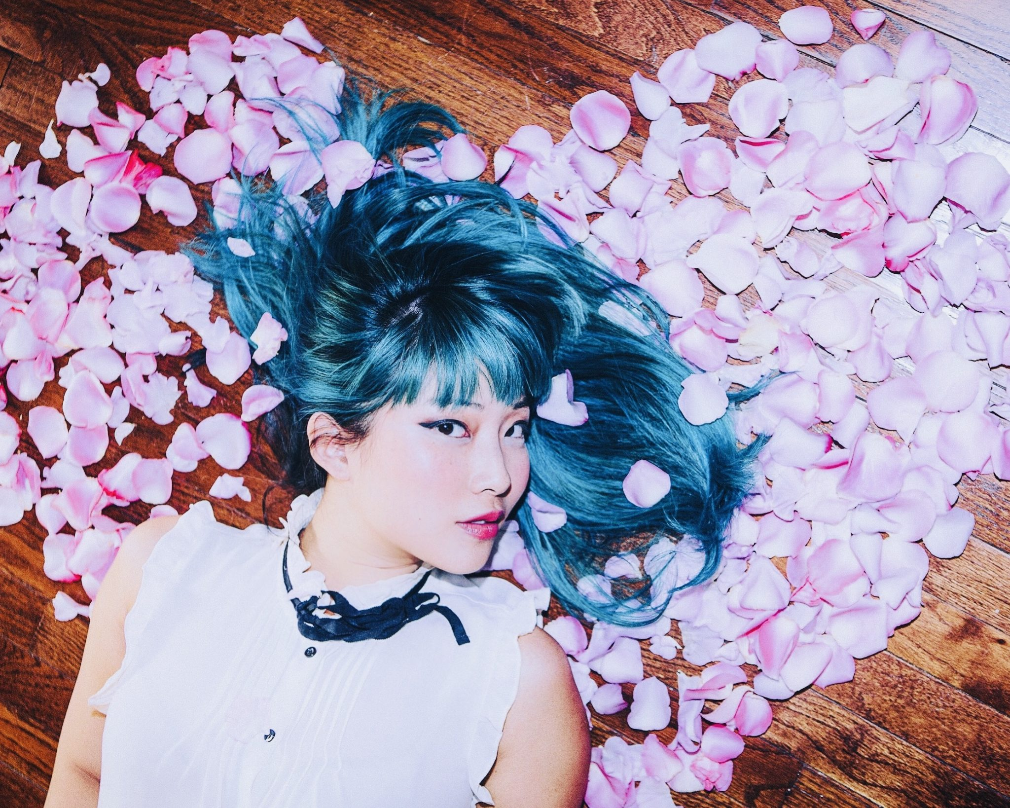 Colour cropped photograph of Polartropica. They are laying on a brown wooden floor with pink petals surrounding them. Their hair is turquoise blue, long and spread around them, with a fringe. Their head is leaning to one side. Their facial expression is neutral. They wear bright pink lipstick and a dark winged eyeliner. They have a white sleeveless blouse on with buttons and black ribbon detail at the top.