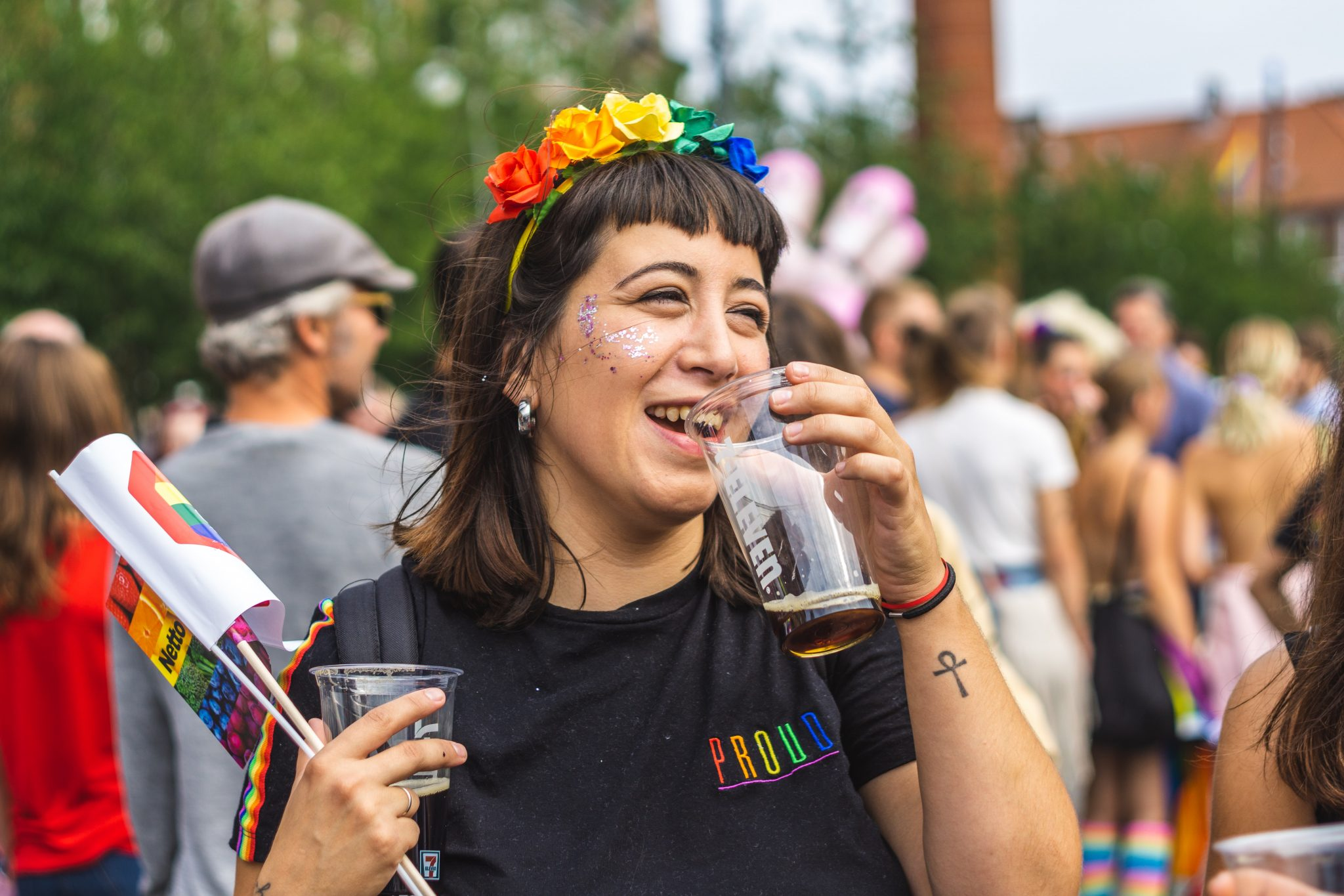 """A woman is at a Pride parade. She has shoulder length dark hair and is holding 2 drinks, one raised to her mouth as she's smiling. In the other hand, she's also carrying a couple of rainbow flags. She's wearing a black shirt that says """"proud"""" in rainbow letters, and has a rainbow flower crown on her head. She also has glitter on her face. The crowd behind her is blurred."""