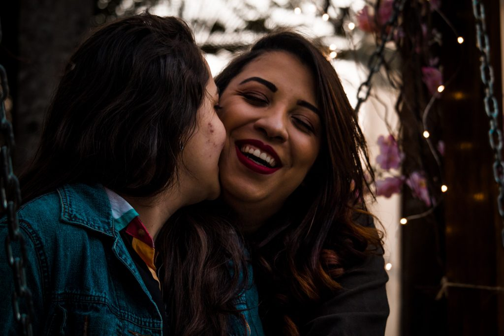A woman of colour smiles as another woman kisses her on the cheek.