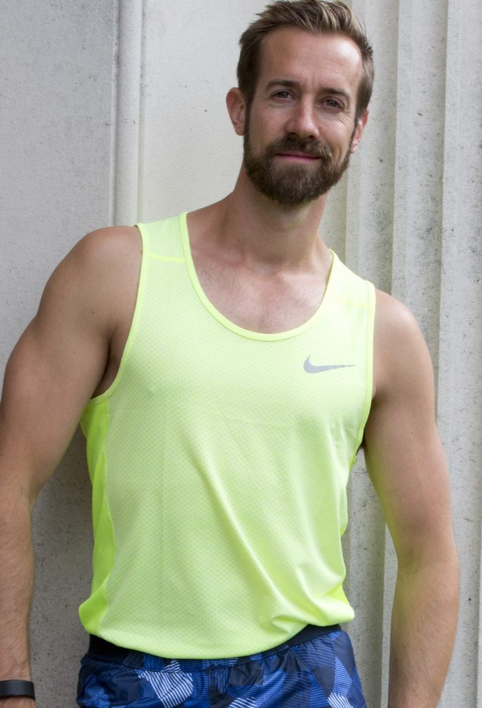 A gay white man wearing a neon green tank top and blue shorts is lightly smiling at the camera.