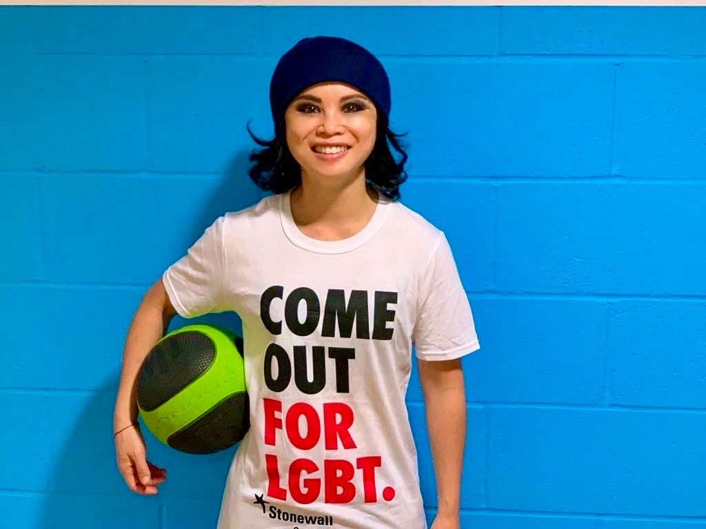 Amazin is wearing a beanie and clutching a flourescent basketball, standing in front of a bright blue brick wall, and smiling as she wears a Stonewall T-shirt that says 'Come Out For LGBT'