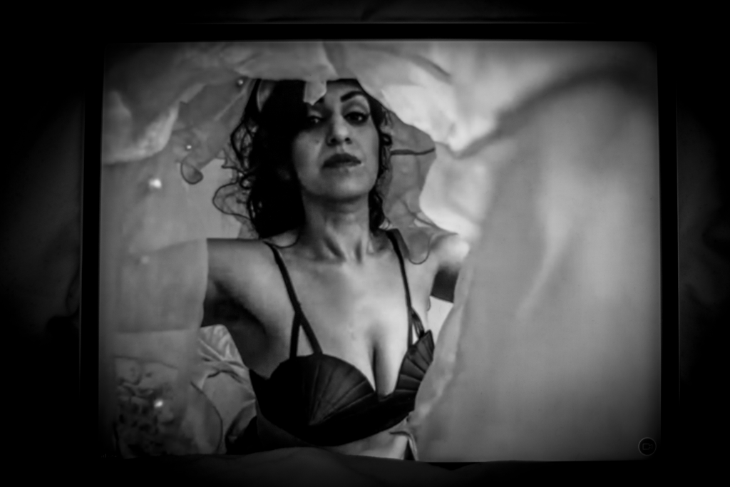 Black and white landscape image. We see a person wearing a shell-like bra. They appear to be in a tunnel of material - as if the camera is peering under the duvet cover. They have dark hair, lipstick on and make up. They are further back in the image as the positioning of the covers makes them seem further away from the camera.