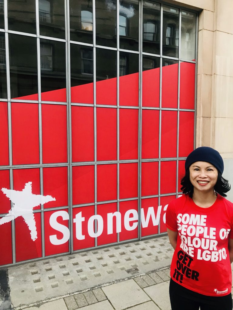 Amazin is standing front of a giant red Stonewall sign, looking at the camera, and wearing her 'Some People Of Colour are LGBTQ Get Over It!' t-shirt with a proud smile.