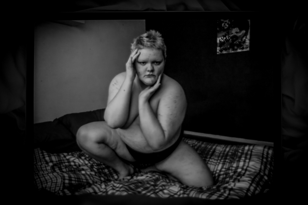 Black and white landscape image. We see a person on their bed. They have one leg bent down on the bed and one bent up to lean towards. They have both arms covering their breasts and framing their face. They are only wearing pants. They have short hair. Their bedding is patterned and the walls behind them are a different colour each, one light and one dark. There is artwork hanging on the wall also.