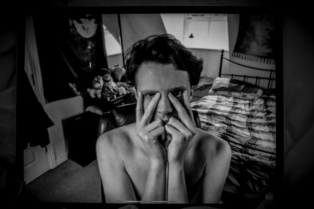 Black and white landscape image. We see a topless person holding their face in their hands looking towards the camera. They have their fore and middle fingers on either side of their eyes to look out. They have short wavy hair. They are in a bedroom. There is a bed to the right of the image with cheque patterned bedding, to the left is storage and cuddly toys. There is a window behind them bringing in light.