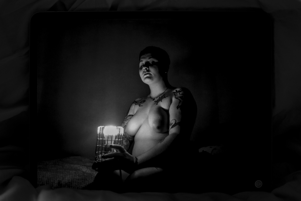 Black and white landscape image. We see a naked body in the centre holding a caged light. The light illuminates their chest, boobs and some of their face. They are sitting on a bed. The background is dimly lit. Their upper chest and arms are covered in tattoos. They have short, shaved hair.