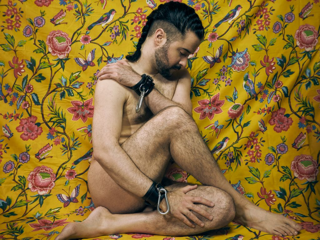 A Bi white Hispanic man is posed in front of a colorful yellow backdrop with leather cuffs on his wrists that end in large metal carabiners. His hair is done in a long French braid with an undercut.