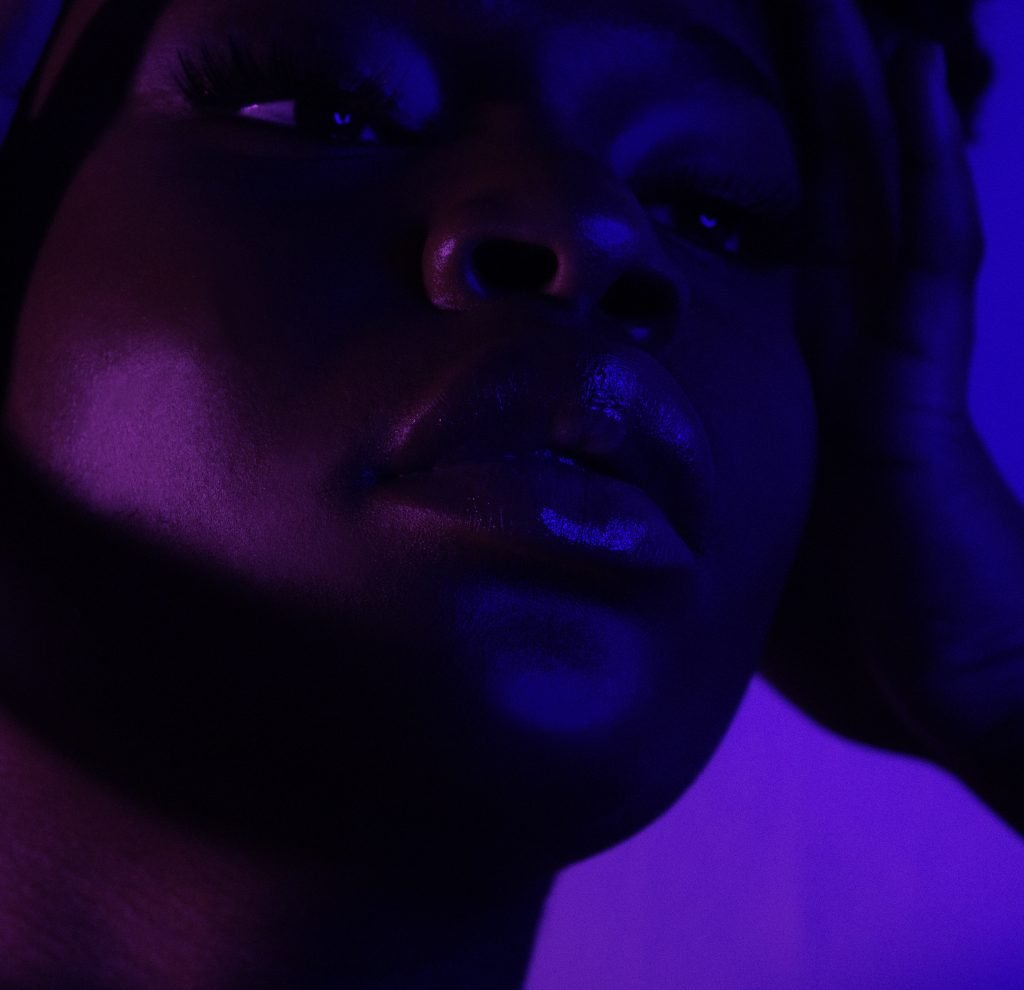 A closeup of a queer Black woman's face with purple lighting.