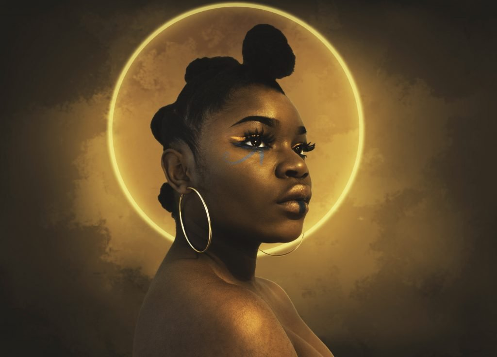 A queer Black woman wearing beautiful eye makeup and gold hoop earrings stares off into the middle distance. Their shoulders are bare and a misty golden halo encircles their head.