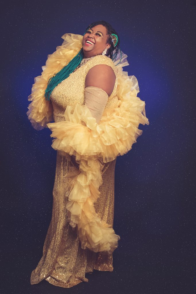 A tall black woman (Lady Blue Phoenix) standing side on to the camera in a floor-length fluffy and sequinned yellow dress. The woman is looking upwards and smiling and looking really happy. The person has dark hair with green ends.