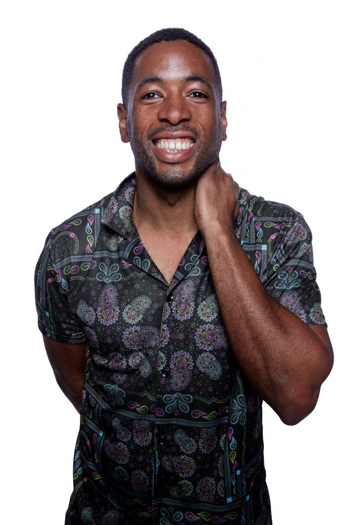 A bi Black man wearing a colorful paisley button-up shirt is smiling at the camera.