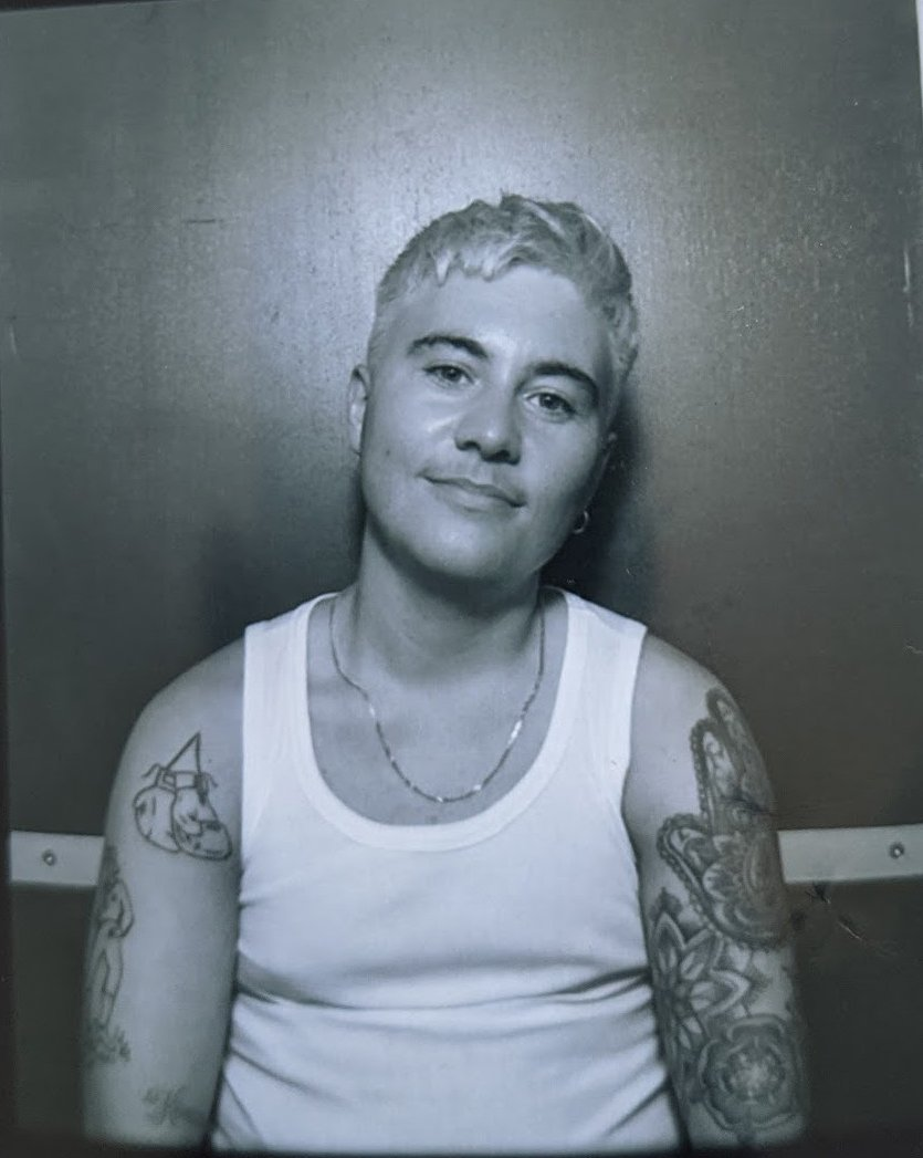 Black and white portrait photo of Paddy from head to midriff. They have bleached short hair and wear a silver chain necklace and white tank top. They have different tattoos across their bare arms. The background is plain, looks like a photobooth. A light source comes from above them.
