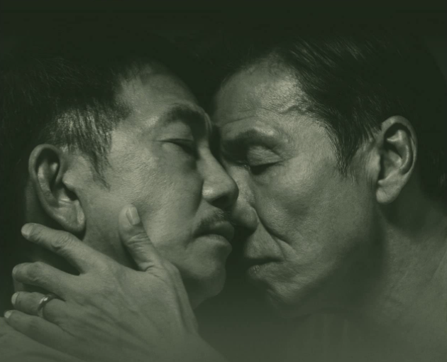 An older man tenderly touches the face of another old man, both of whom have their eyes closed