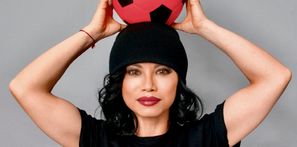 Amazin is a Vietnamese woman with a modellesque face, a piercing hazel-eyed stare and bright red lips. She is lifting a red football onto her head, resting on her black beanie which flows into her black bob which flows into her black T-shirt
