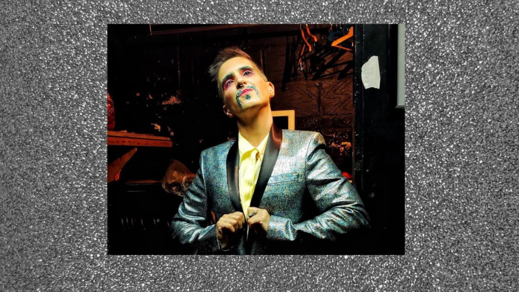 A picture of a slim white king with a teal glitter moustache and matching eyebrows standing in a doorway looking up. They have spiky brown hair and a big nose. They wear a tan blouse under a shimmery blue dinner jacket.