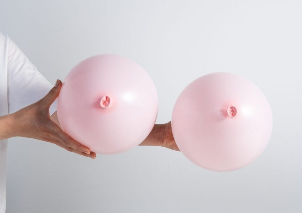 Two pink balloons being held out, the tie at the bottom facing the camera to show the boob-esque shape of them.