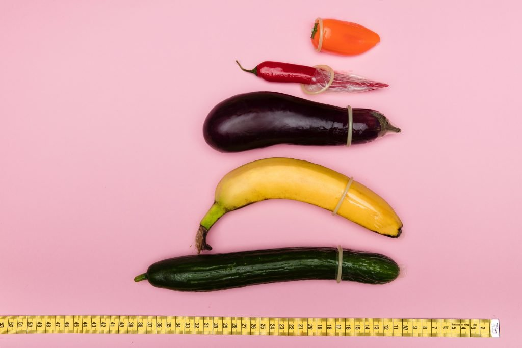 On a pink background next to a tape measure, phallic fruits and veg (ranging from a tiny pepper to an aubergine up to a massive cucumber) are lined up. They are all inserted partially into a condom, and bend in different ways, just like willies do.