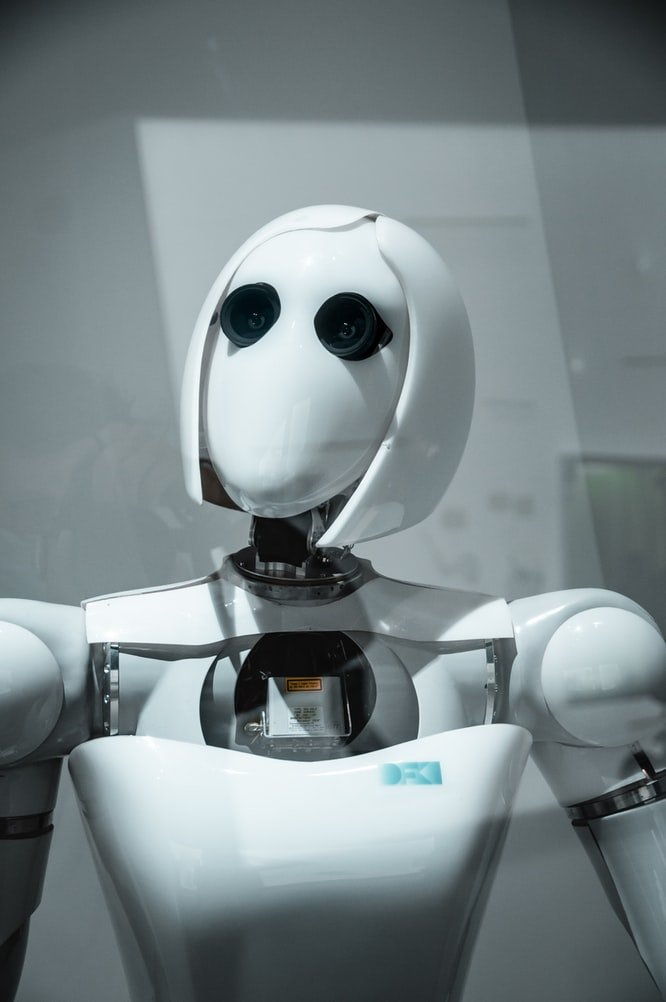 a white robot with a short hair cut looks into the distance