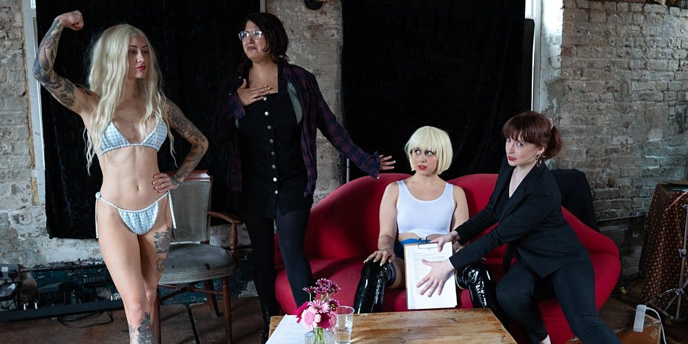 in a quasi-comical pose, there are four sex-workers from Sexquisite Events from left to right. The furthest left is muscly, tattooed and in a bikini, flexing her muscles with her long blonde hair. Next right is a demurely dressed woman, looking faux-shocked but clearly also raring to get stuck in. Next is a woman in a short bob and thigh highs, sitting on a red sofa looking at the bodybuilder with her legs wide apart. The gap between her legs is covered by a clipboard, held by the business woman to her right who is looking knowingly at the camera.